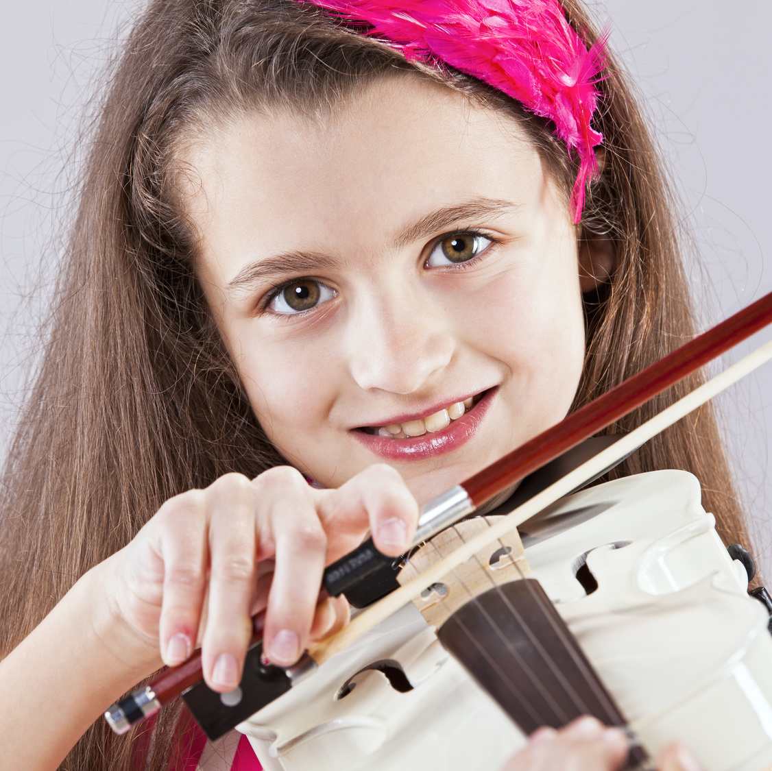 Female child playing the violin with gray background